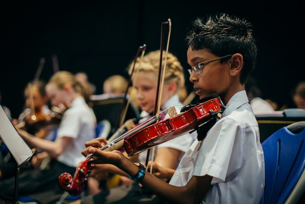 A group of young people playing the violin.
