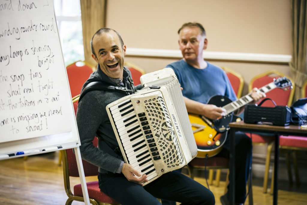 Musician Luke Carver Goss smiling and holding the accordion in a darts music workshop