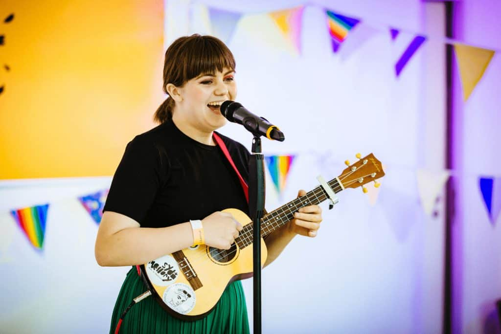 A girl singing and playing guitar